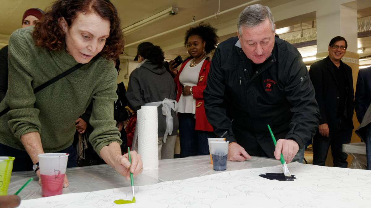 Mural Arts Program Executive Director Jane Golden and Mayor Jim Kenney work on one of the canvasses. (Bastiaan Slabbers/for NewsWorks)