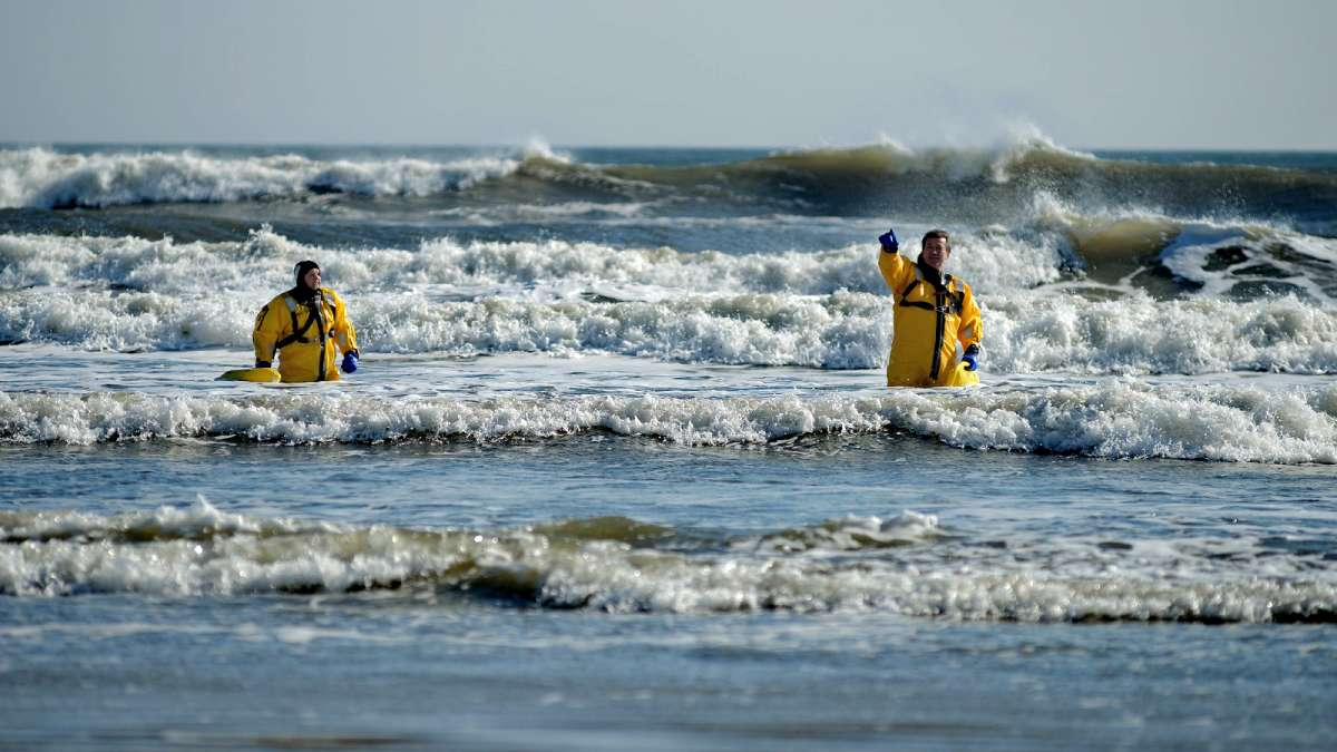 Divers of Wildwood and Middle Township Police Departments stand waist deep in the surf as they wait for the plungers to hop in. (Bastiaan Slabbers/for NewsWorks)