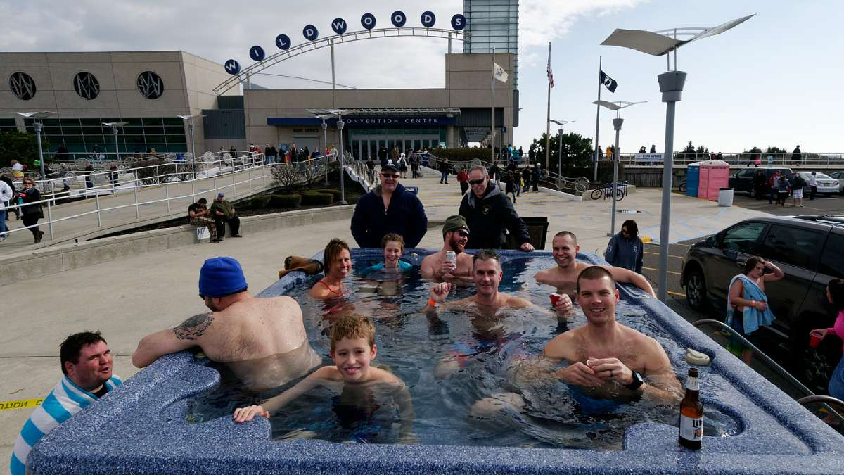 After a dip in the 48 degree ocean police officers with families warm up in a hot tub, set up by Scott Jarvis (not pictured) outside the Convention Center. (Bastiaan Slabbers/for NewsWorks)