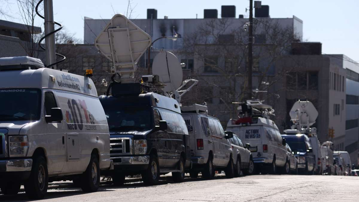A large number of news vans line both sides of Swede Street, on the west side of the courthouse.