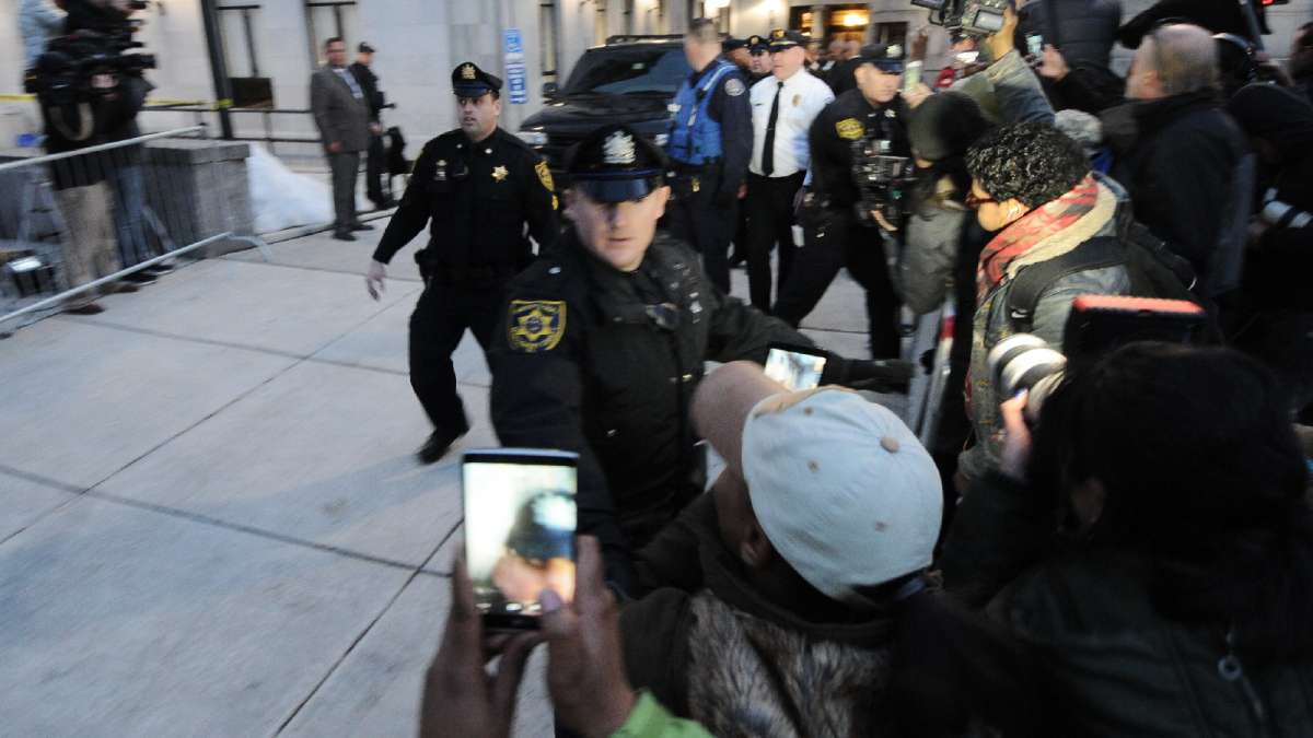 Police try to clear the sidewalk as the black SUV carrying Cosby leaves shortly after the hearing is adjourned for the day.