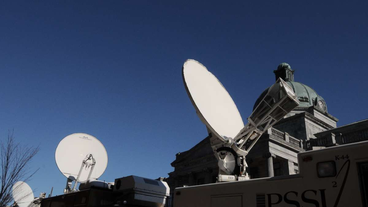 Satellite vans responsible for transmitting live feeds have their dishes pointed skywards.