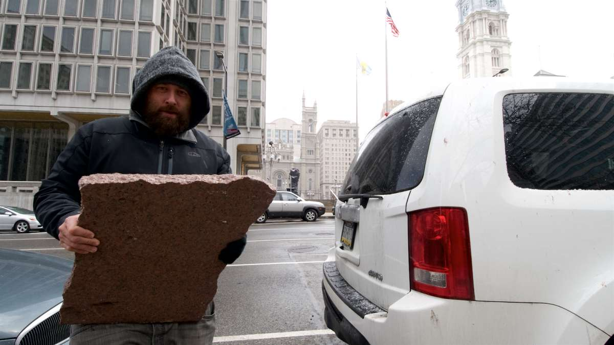 Ryan Gee hauls a sizable piece of red granite to the trunk of his car. He wants to bring it home as a keepsake.
