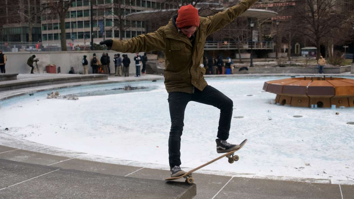 Scott Mantua of Jim Thorpe, Pennsylvania performs tricks on a ledge around the fountain base as he tries to keep on riding throughout the snow.