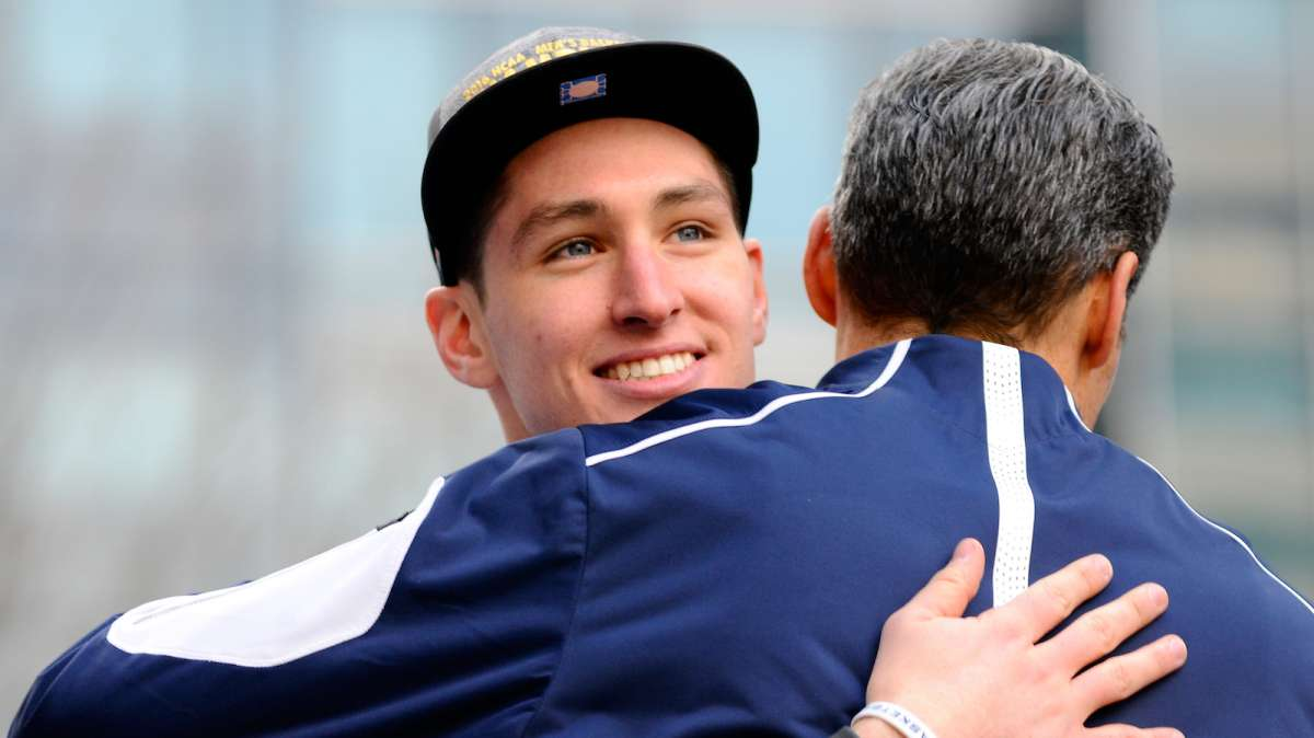 Wildcats' Ryan Arcidiacono embraces Head Coach Jay Wright as he looks at the crowds gathered for the ceremony.