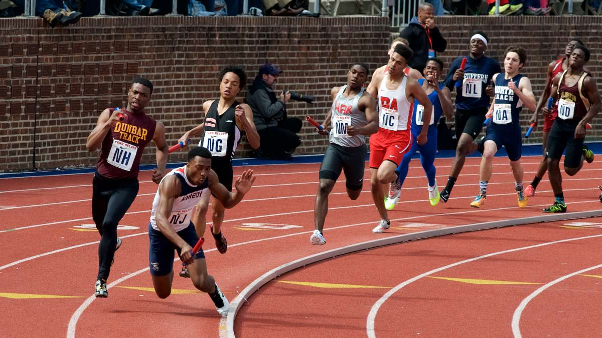 A runner trips over the rail as he competes in one of the high school events.