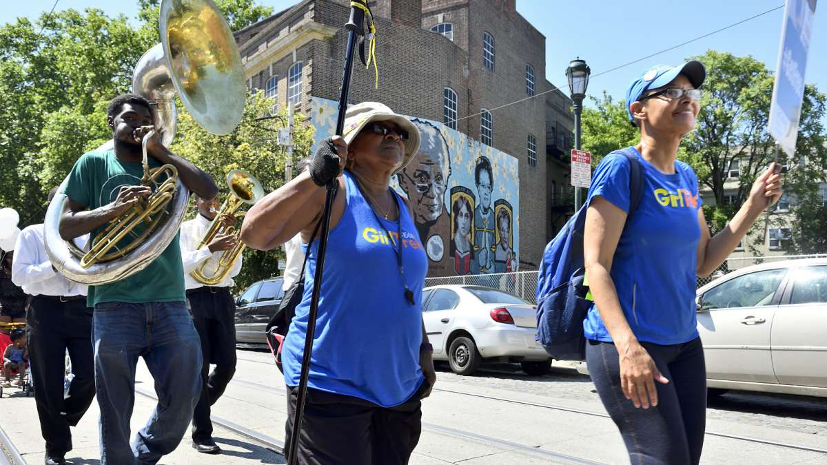 The parade marches past the Women of Germantow mural on the side of the Germantown YWCA as it heads towards the Juneteenth Festival, near Johnson House.