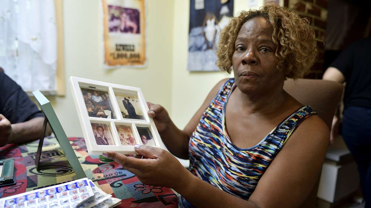 Michelle Witherspoon holds up a picture frame with photos of Kenyada Jones.