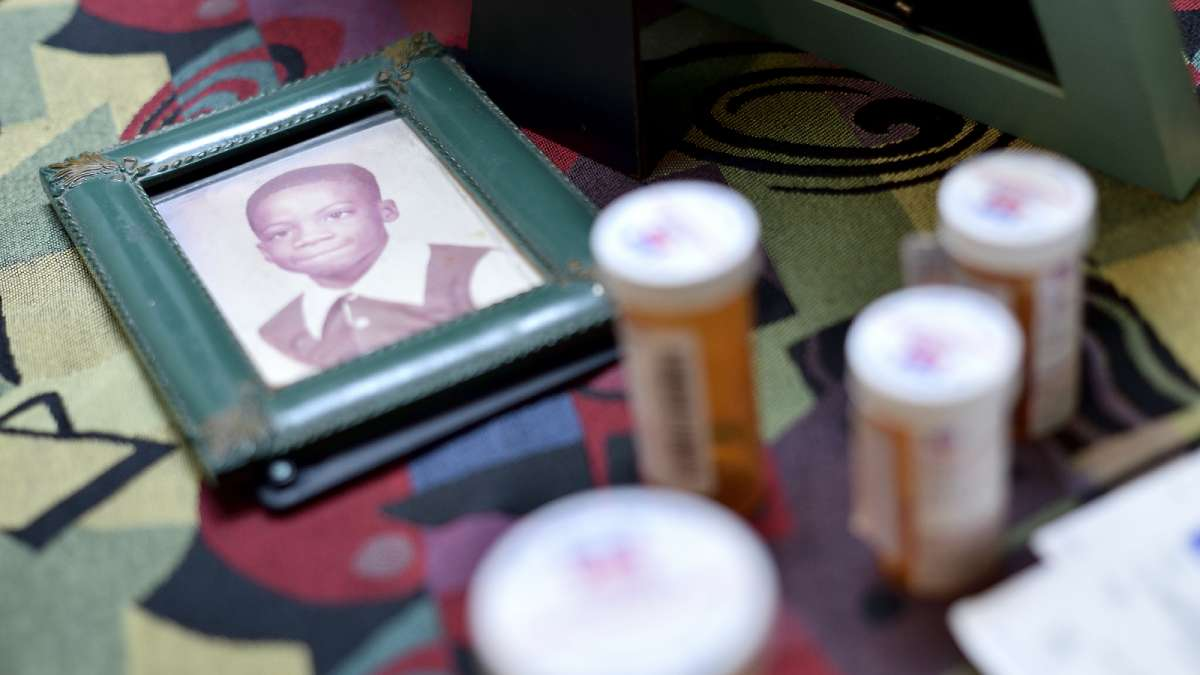 Surrounded by medicine canisters, a photo of Kenyada Jones as a young boy lies on the dinner table at his mother's house.