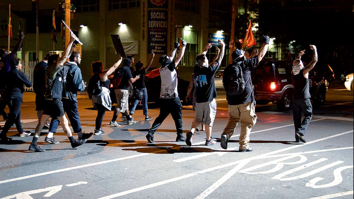 Protesters, including at least four unidentified British men (seen on the right) gesture into the spotlight from the PPD helicopter.