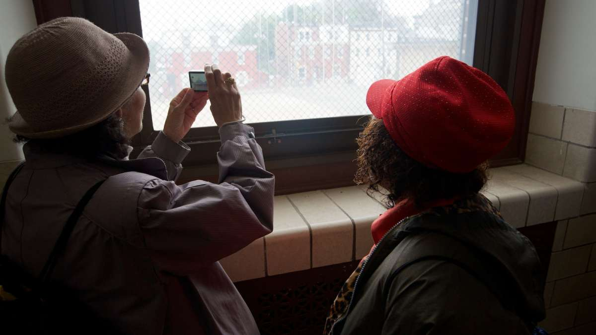 Visitors capture an image of the neighborhood as seen from inside the shuttered Fulton Elementary School on East Haines Street. (Bas Slabbers/for NewsWorks)