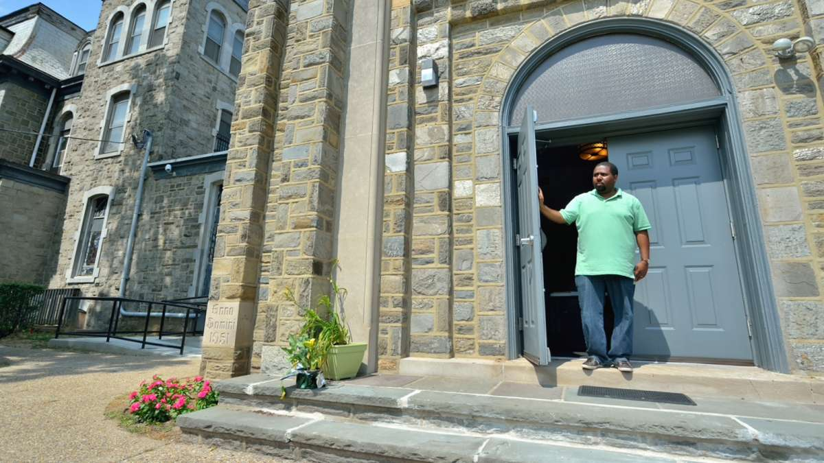 Karim Rogers holds open the door of a former church that now houses a performing-arts center on the Germantown Settlement campus, located in the 4800 block of Germantown Ave. (Bas Slabbers/for NewsWorks)