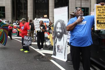 Protesters call for the release of Mumia Abu-Jamal, convicted in 1982 of murdering a Philadelphia police officer, chant outside the Philadelphia District Attorney's Office. (Emma Lee/WHYY)