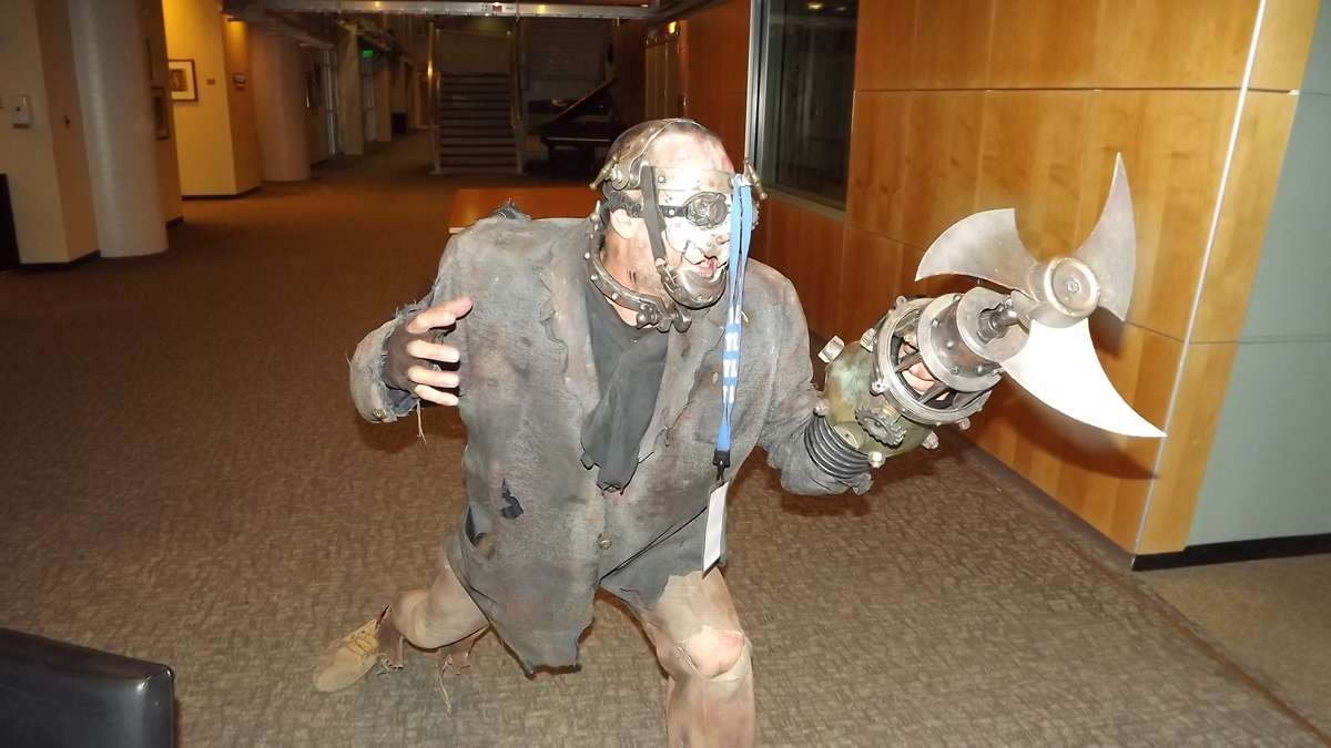 Scary zombie guy, dangling his visitor badge from a knob on his head, twirls his blade and strikes a pose at WHYY studios. (Jeanette Woods/WHYY)