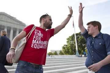 Gay rights activist Bryce Romero, of the Human Rights Campaign, offers an enthusiastic high-five on Wednesday to visitors getting in line to enter the Supreme Court before justices handed down major rulings on two gay marriage cases that impact same-sex couples across the country. (AP Photo/J. Scott Applewhite, file)