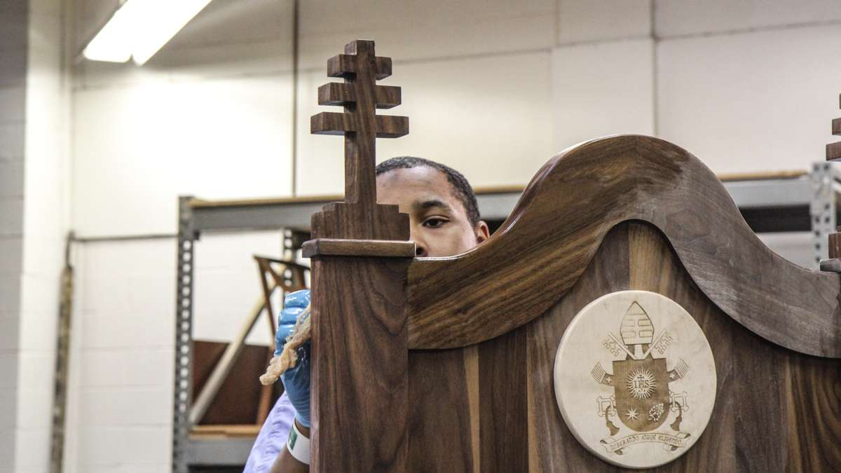 Inmate Hakim Burke varnishes the chair made for Pope Francis at Philadelphia Industrial Correctional Center. (Kimberly Paynter/WHYY)