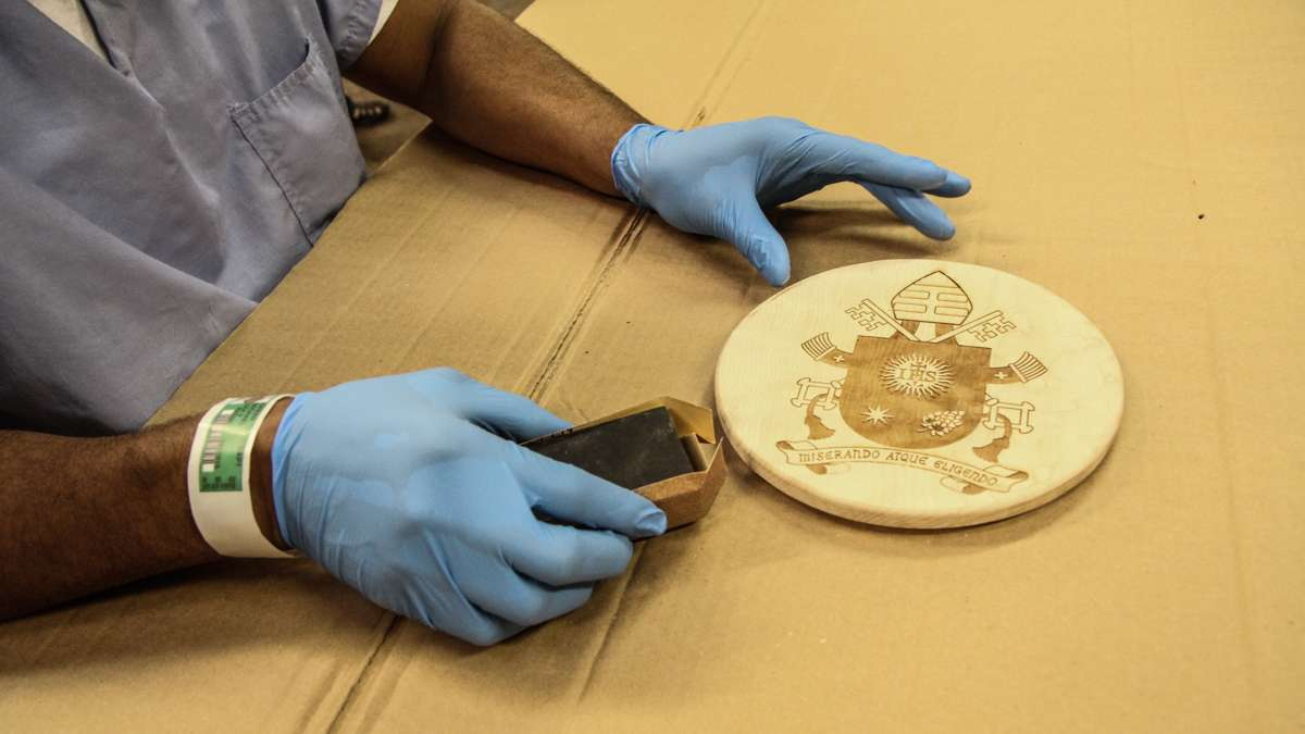 Michael Green sands the seal to be placed on the pope's chair. (Kimberly Paynter/WHYY)