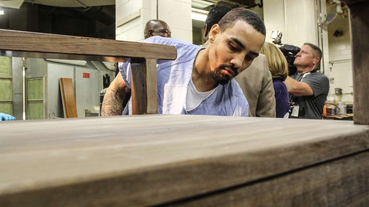 Inmate Evan Davis sands the chair that Philadelphia inmates are making for Pope Francis. (Kimberly Paynter/WHYY)