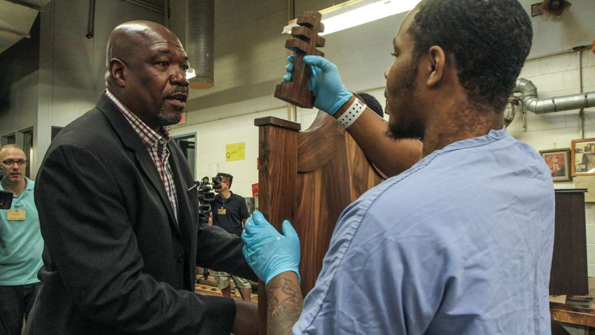 Chair Designer Anthony Newman instructs an inmate on where to place one of the chair's crosses. (Kimberly Paynter/WHYY)