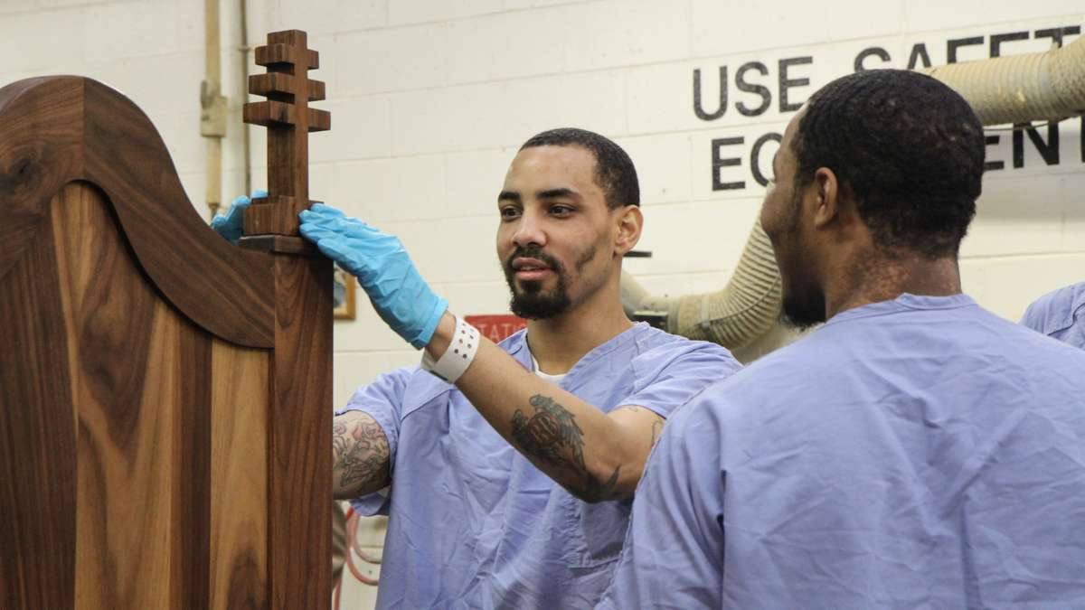 Inmate Evan Davis installs one of the chair's crosses. (Kimberly Paynter/WHYY)