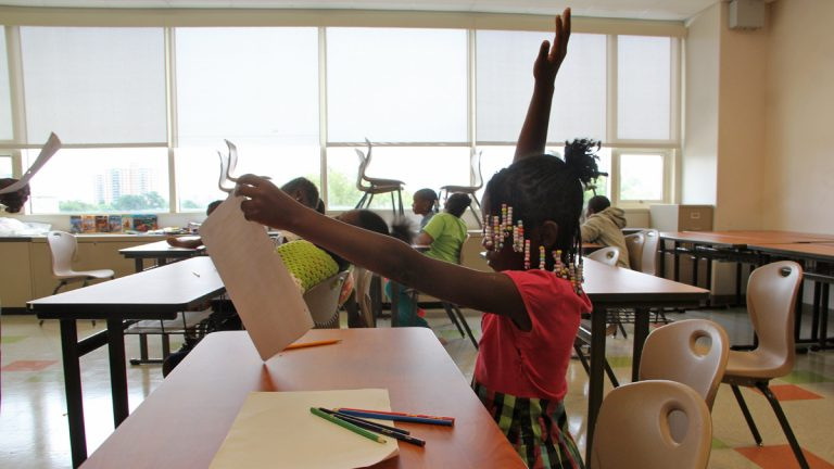 "A student raises her hand during a summer reading program at West Philadelphia school. (Emma Lee/WHYY) Check out our series of podcasts and web ""explainers"