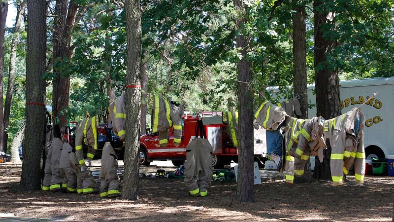 Fire fighters' protective suits hang in a shady grove at the 37th Annual Fire Apparatus Show and Muster at WheatonArts, in Millville, NJ, on Sunday. (Jana Shea for NewsWorks)