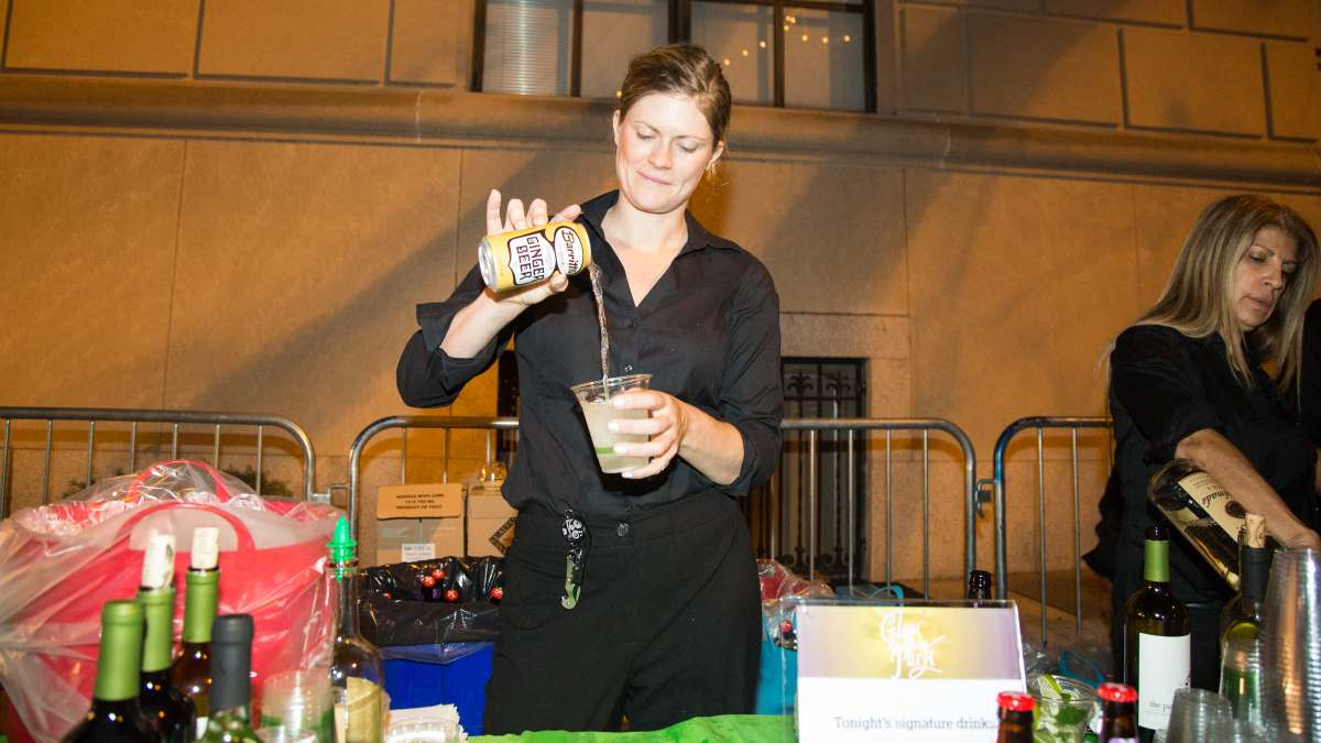 A bartender makes the night's signature drink, a Moscow Mule, with Tito's Homemade Vodka and Barritt's Ginger Beer.