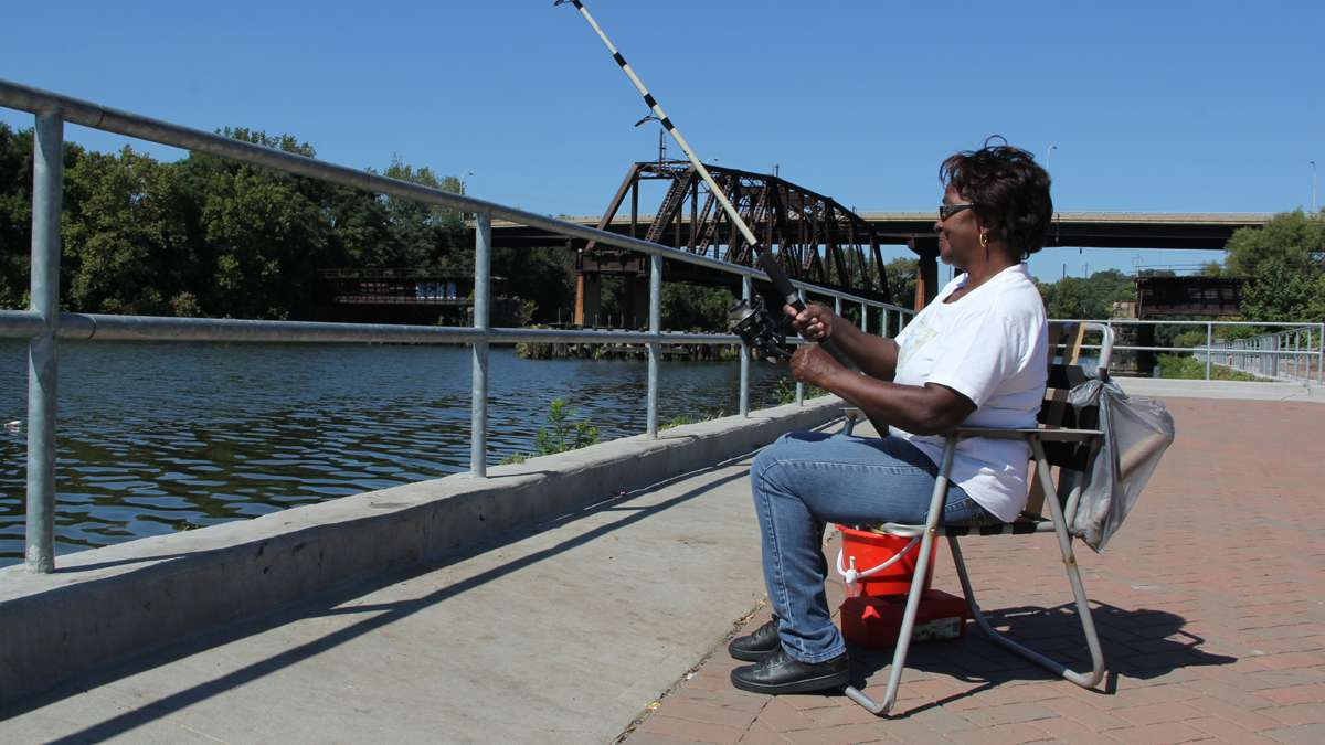 Estelle Terrell enjoys a day of fishing on the Schuylkill River at Grays Ferry Crescent. (Emma Lee/for NewsWorks)
