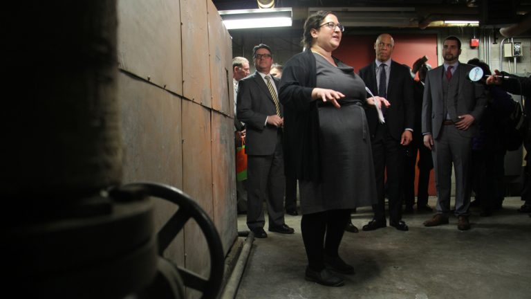 Emily Schapira, executive director of the Philadelphia Energy Authority, talks to reporters in front of an old boiler in the basement of Lankenau High School, an example of the kinds of improvements that could be made under the Energy Pilot Project. (Emma Lee/WHYY)