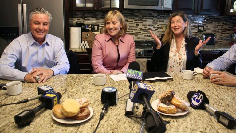 Republican nominee for New Jersey governor Kim Guadagno (center) promises lower property taxes during a press event in the suburban kitchen of Rennie and Phil Wessner. Seated to Guadagno's right is Evesham Mayor Randy Brown and on her left is homeowner Rennie Wessner. (Emma Lee/WHYY)