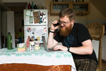 Alex Spencer sits at his table making phone calls to be a test subject for new studies. (Paige Pfleger/WHYY)