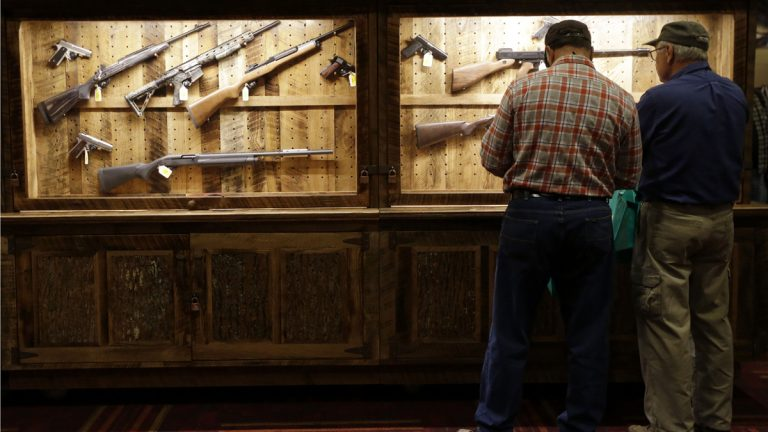 File image of attendees looking over a wall of guns available to win in a raffle at the National Rifle Association's annual convention in Friday