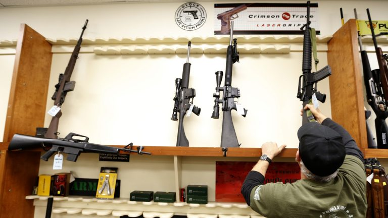 File photo of Mike Fiota, Duke's Sport Shop store manager, replacing one of the five military style rifles available into the rack that usually has more than 20 new models for sale in New Castle, Pa. (AP Photo/Keith Srakocic)
