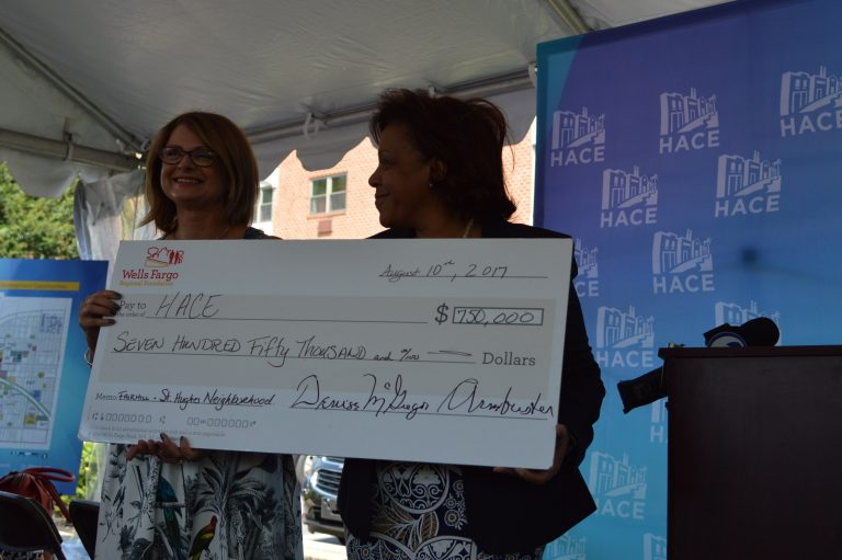 Denise McGregor-Armbrister (right) of the Wells Fargo Regional Foundation presents a check to HACE President Maria Gonzalez for use in redeveloping the Fairhill-St. Hugh neighborhood.   (Tom MacDonald/WHYY)