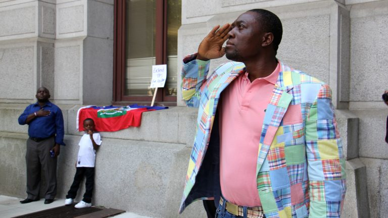 Haitians salute as their country's flag is raised in front of City Hall during Haitian Flag Day,  May 18. The federal government has extended temporary protected status  for Haitians living in the U.S. (Emma Lee/WHYY, fie)