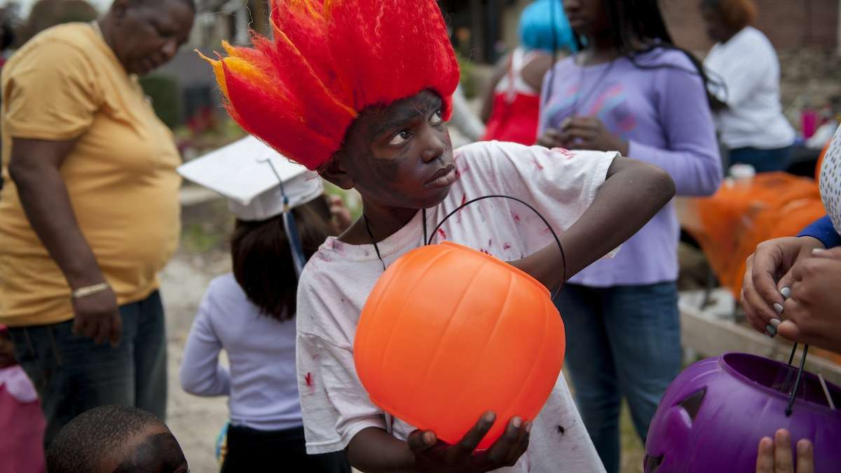 Kevon Lewis, 9, of Germantown, loaded candy into a pumpkin to be given away as prizes at the Halloween party for West Rockland Street in Germantown on Halloween night. (Tracie Van Auken/for NewsWorks)