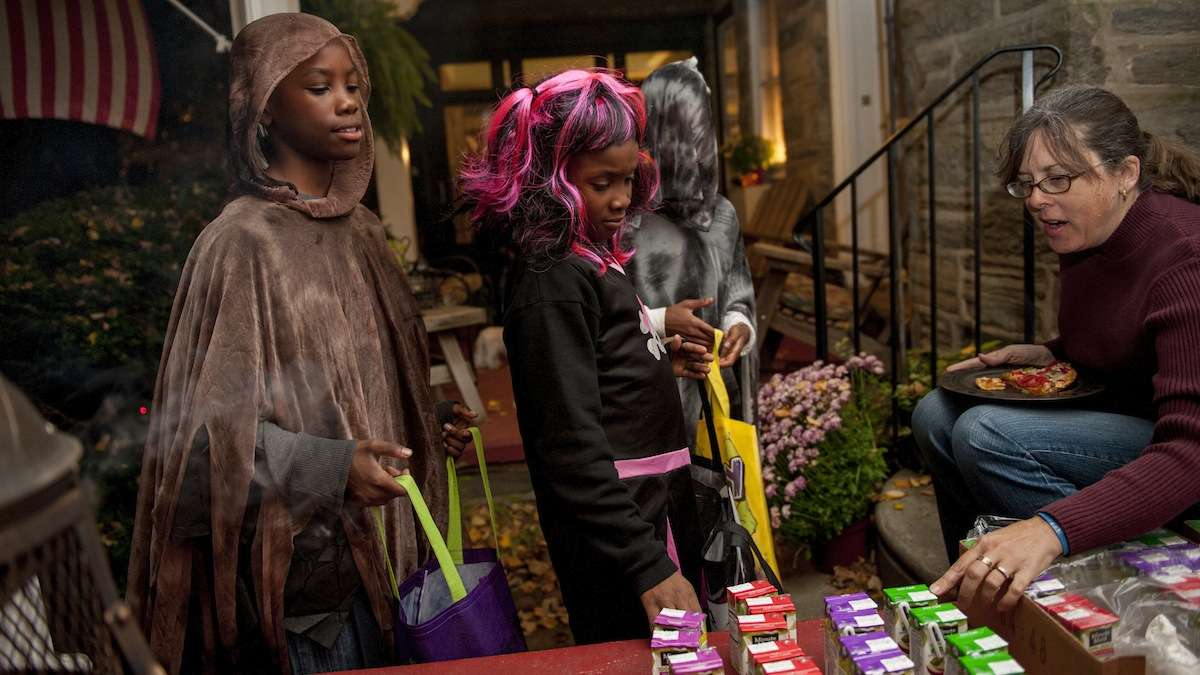 Robin Vallette sits on her porch in Chestnut Hill and gives juice boxes away to trick-or-treaters (from left) Darrius Ward, 11, Daysha Ward, 8, and Taren Williams, 12, all from Chestnut Hill, on Halloween night. (Tracie Van Auken/for NewsWorks)