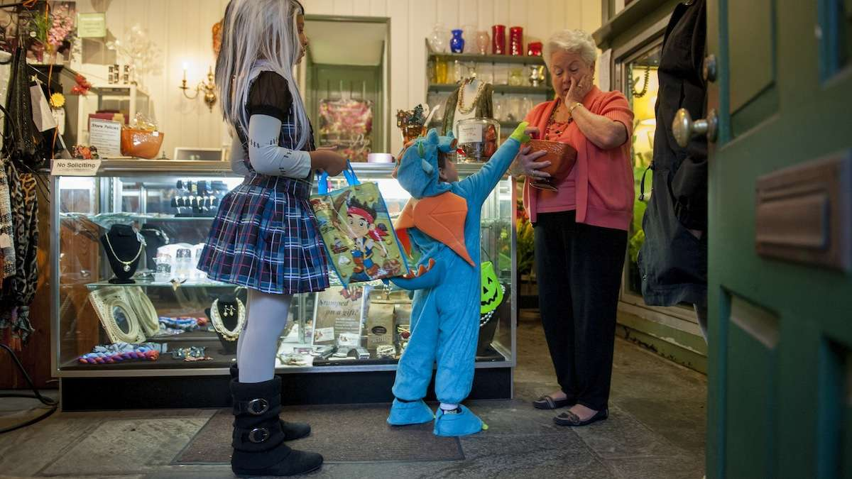 Yandel Aponte-Boyd, 3, of Mt. Airy, startles Linda Rothe, with Rothe Florists, when he comes back for seconds while trick-or-treating at the shops on Germantown Avenue Halloween night. Next to him is Leilanni Mays, 10, of East Oak Lane. (Tracie Van Auken/for NewsWorks)