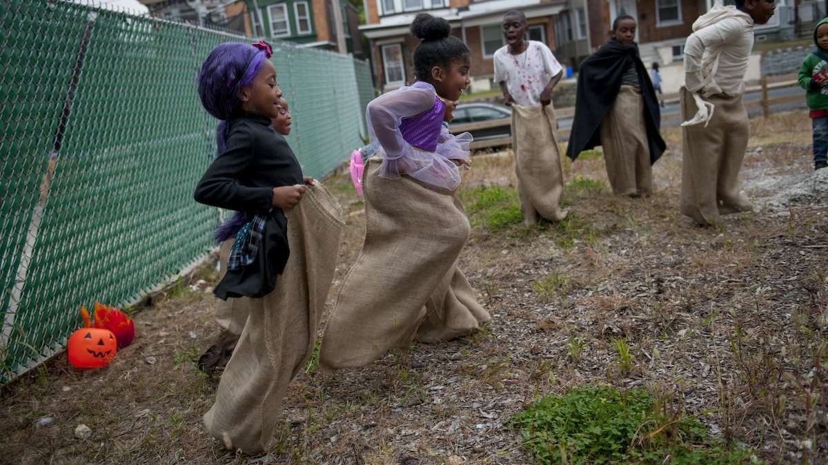 Cymaiah Marc (left), 6, and Makayla Oduardo (center), 6, participate in a potato sack race during the West Rockland Street Halloween Party in Germantown on Halloween evening. (Tracie Van Auken/for NewsWorks)