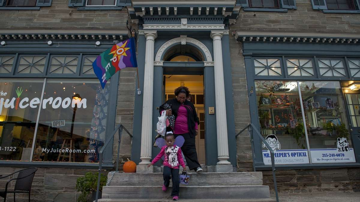 Ruth Stroman, of Mt. Airy, and her daughter Madison, 3, leave The Juiceroom after trick-or-treating there on Halloween evening. (Tracie Van Auken/for NewsWorks)
