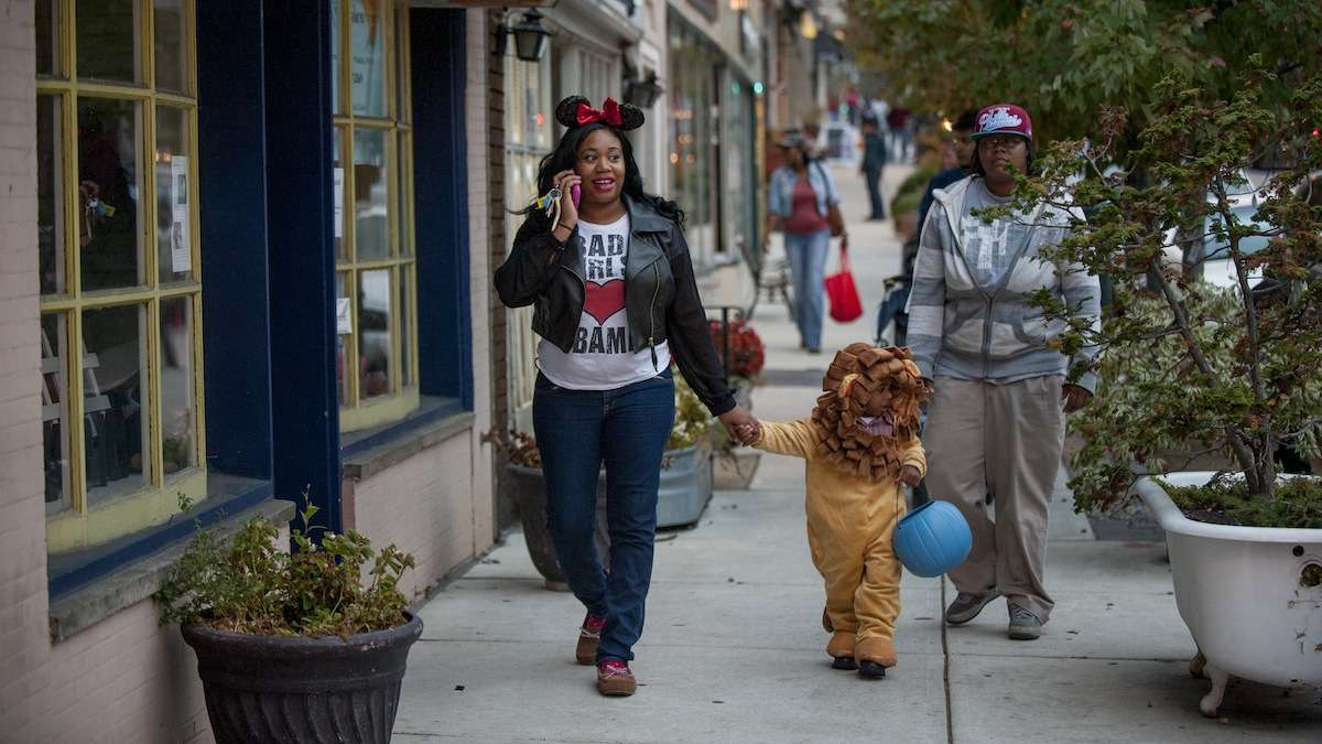 Tyrena Jackson (left), of Mt. Airy, takes her son Zaiking Jackson, 2, trick-or-treating at the shops on Germantown Avenue with Rashea Martin (right) on Halloween night. (Tracie Van Auken/for NewsWorks)