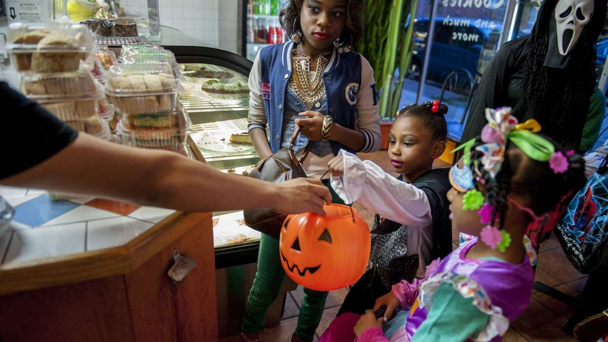 Saige Frazier (center), 5, of Mt. Airy, gets candy at Mi Puebla Mexican Food Restaurant on Germantown Avenue Halloween night. With her are her sister, Amanda Frazier (left), 10, and Kya Conyers (right), 5. (Tracie Van Auken/for NewsWorks)