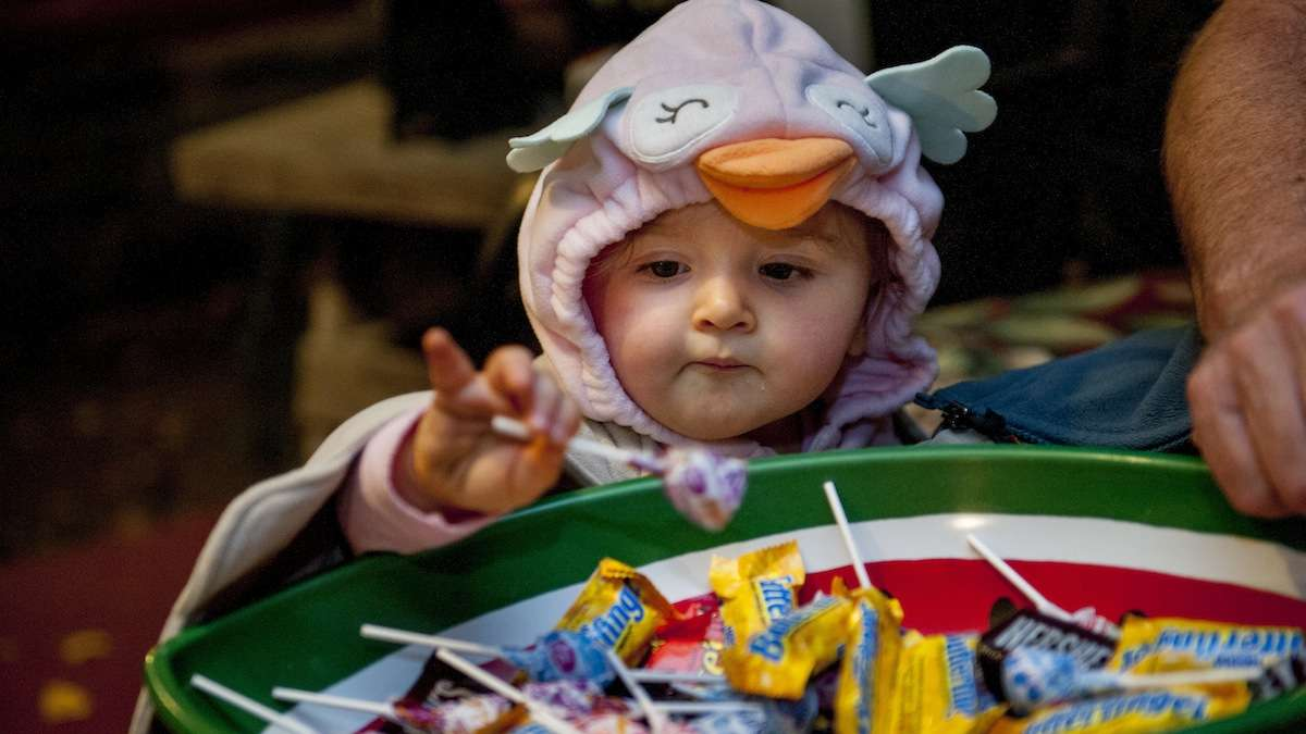 Evie Valiante, 18 months, takes a lollipop from Jim McCafferty in Chestnut Hill on Halloween night. (Tracie Van Auken/for NewsWorks)