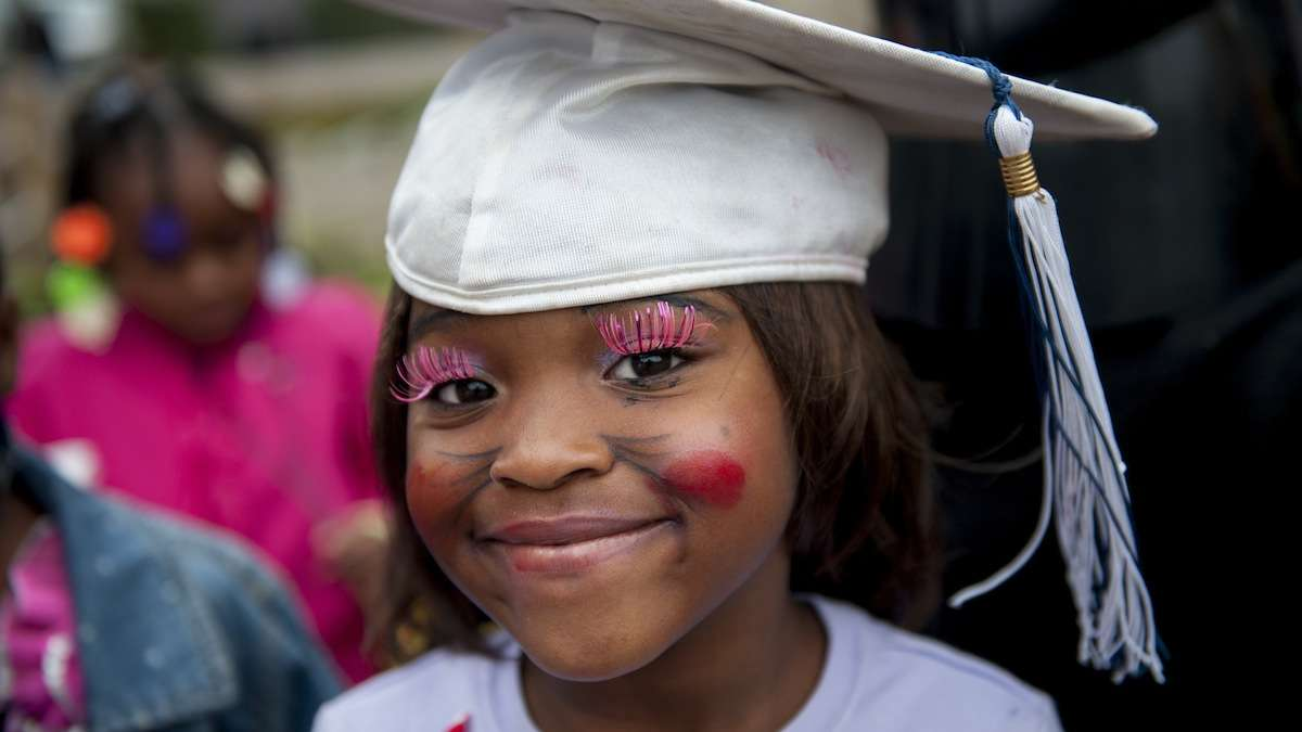 Chiani Reed, 5, wears pink lashes and a graduation cap to the West Rockland Street Halloween party on Halloween night. (Tracie Van Auken/for NewsWorks)