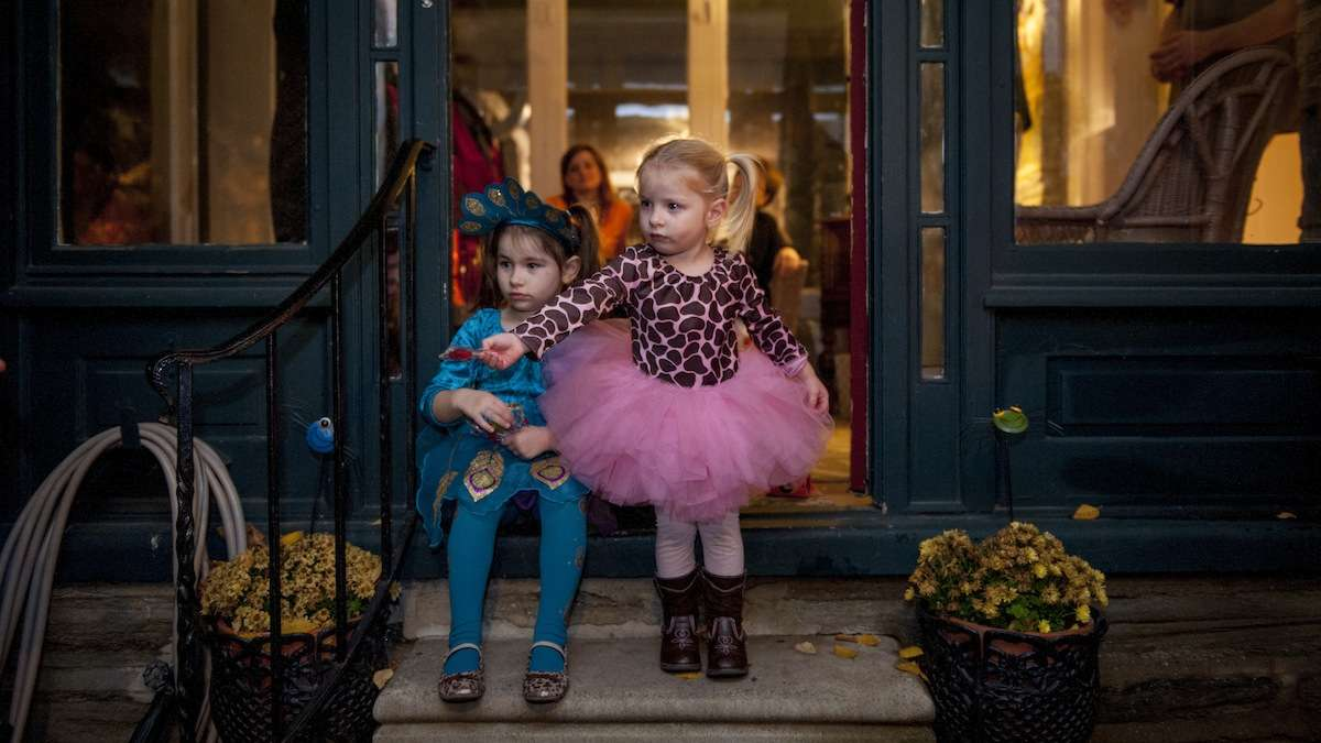 Ava Sylvester, 2, and her sister, Audrey, 4, stand on their front porch in Chestnut Hill and wait to give candy to trick-or-treaters on Halloween night. (Tracie Van Auken/for NewsWorks)