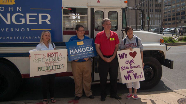 Pa. gubernatorial candidate John Hanger stands in front of his red, white and blue bus with Amy Chen (right) a junior at Science Leadership Academy, and Maureen Smith (left), a junior at CAPA. Both girls sit on the superintendent's advisory board for the School District of Philadelphia. (Ann Marie Awad/for NewsWorks)