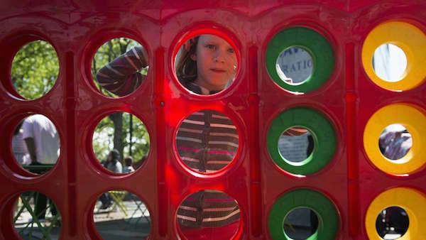 Alma Nikaé stares through the holes of a giant connect four game during opening weekend of the Spruce Street Harbor Park.