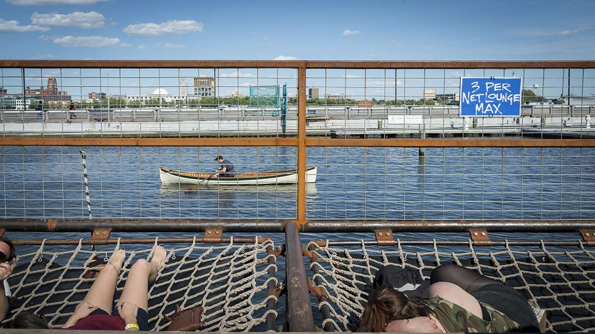 Visitors to Spruce Street Harbor Park sunbathe in nets strung over the water.