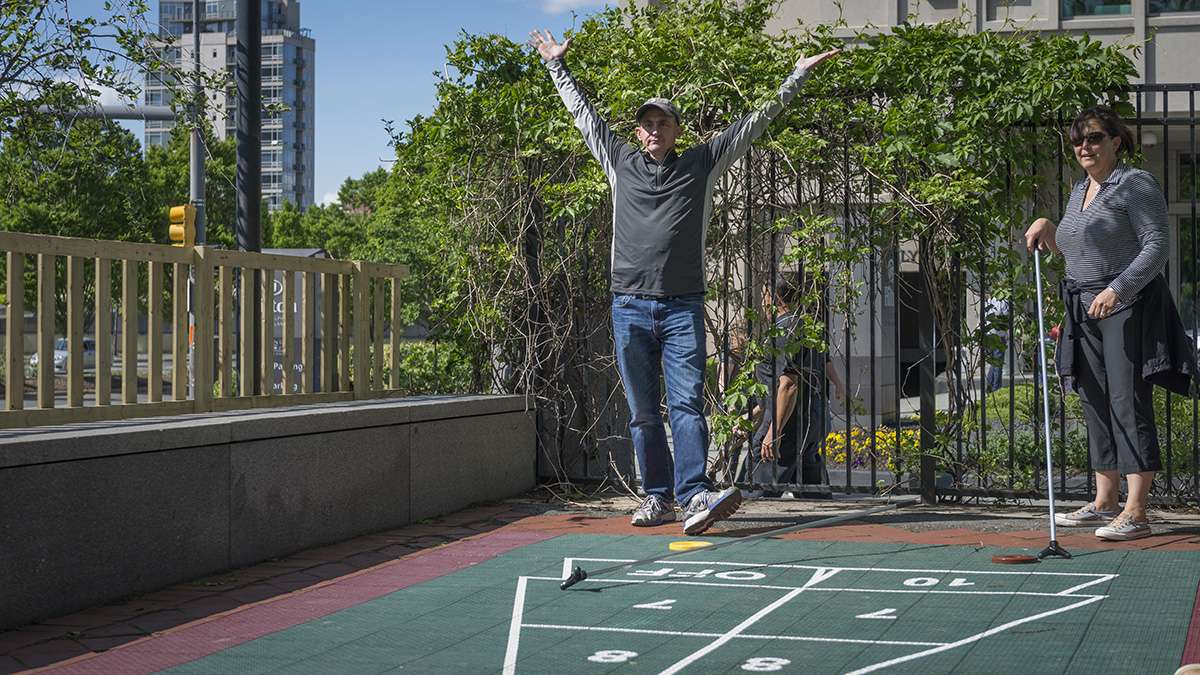Lou Troilo celebrates a shuffleboard victory over family members at the opening weekend of the Spruce Street Harbor Park.
