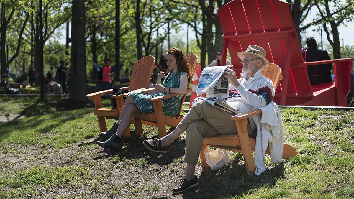 Jay Chaplan reads a newspaper on the banks of the Delaware River during opening weekend of the Spruce Street Harbor Park.